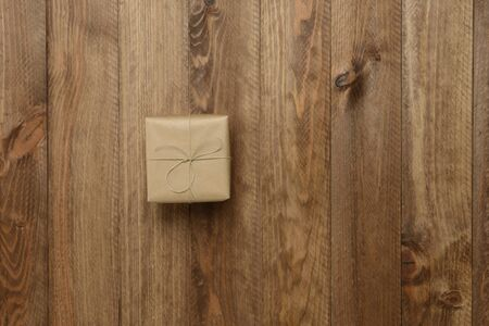 Gift box on wooden background, top view