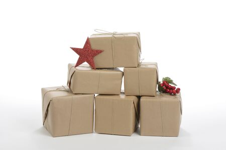 Stacked gift boxes with christmas decoration on white background
