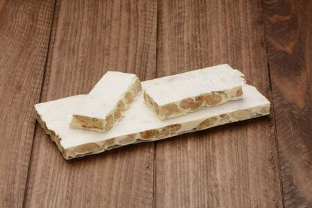 Hard nougat tablet on wooden background, and some pieces
