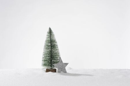 Decorative artificial christmas tree in artificial snow and one gray star, composition as a card or banner