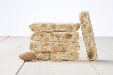 Hard nougat on white wooden background, cut into pieces