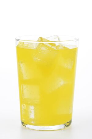 Glass of orange soda with ice on white background Foto de archivo