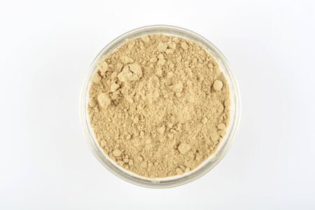 Ginger ground in a glass bowl on white background, top view
