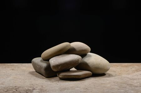 Stacked stones with black background on a stone table Stok Fotoğraf