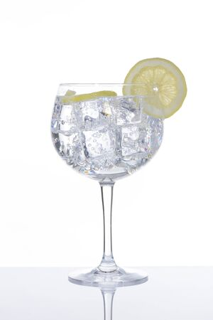 Glass of gin and tonic with a slice of lemon on white background