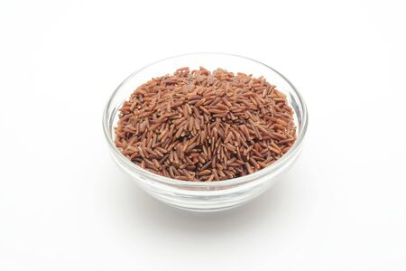 Red wholemeal rice in a glass bowl on white background Imagens
