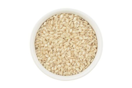 Wholemeal rice in a glass bowl on white background, isolated