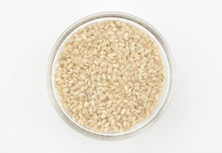 Brown rice in a glass bowl on white background, top view Imagens