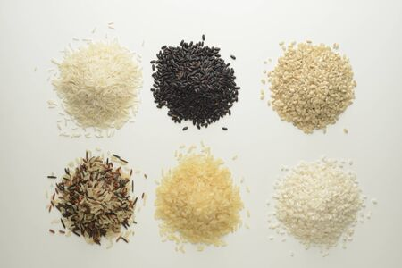 Raw rice on white background, different varieties Imagens