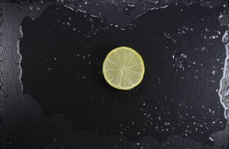 Lemon slice on black stone plate with water splash, top view Reklamní fotografie