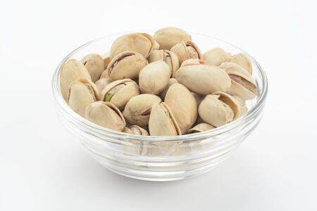 Pistachios in a glass bowl on white background