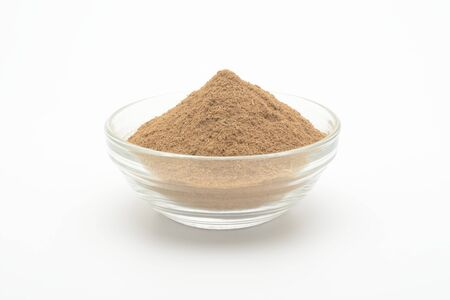 Ground cinnamon in a glass bowl on white background