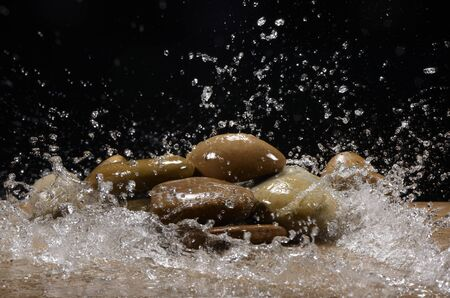 Water falling on some stones with black background