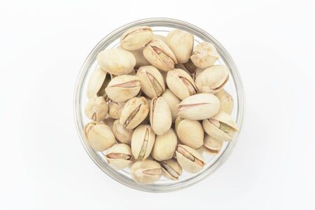 Pistachios in a glass bowl on white background, top view 写真素材