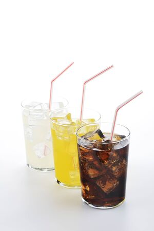 Cola, orange and lemon soda in glass with straw on white background. Refreshing drinks on white background.