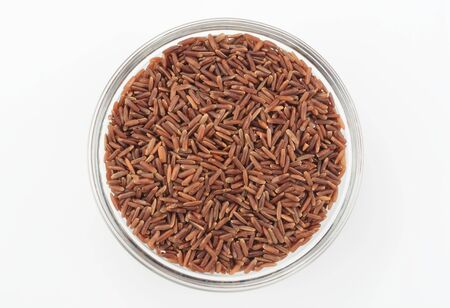 Red wholegrain rice in a glass bowl on white background, top view