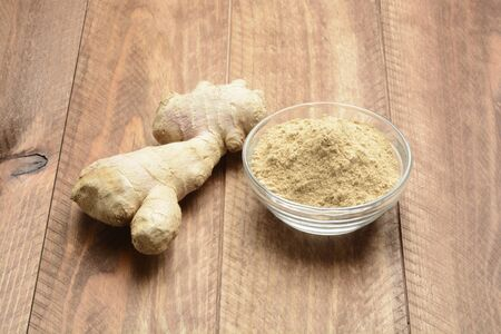Ginger root and ground ina bowl on wooden background
