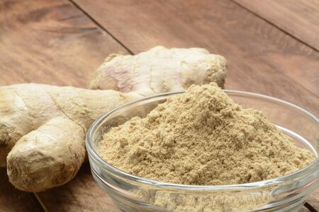Ginger root and ground on wooden background, detail