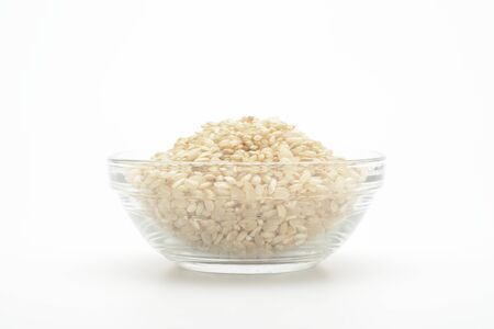 Brown rice in a glass bowl on white background