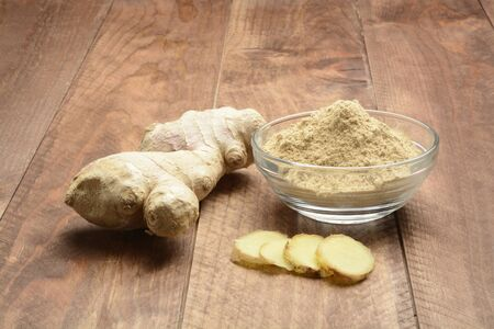 Ginger root and ground on wooden background