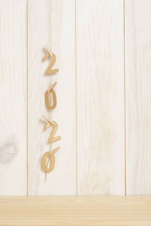 New year 2020 in golden wood numbers hanging on a rope subjects with vertical clamps