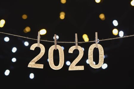 New year 2020 in golden wood letters hanging on a rope with unfocused lights on black background, composition as a postcard