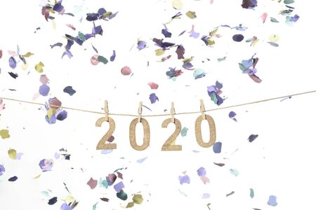 New year 2020 in golden wood numbers hanging on a rope subjects with tweezers and confetti falling