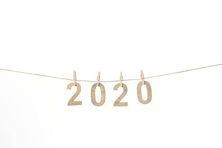 New year 2020 in golden wood numbers hanging on a rope subjects with tweezers
