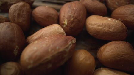 A macro shot of peanuts lying on a wooden surface. Organic healthy food, vegetarianism. Archivio Fotografico