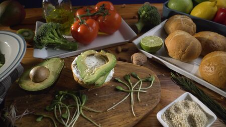 Healthy food. Healthy assortment of vegetables and fruits with legumes: sandwich with avocado and sesame, sprouted grains, fresh bread, lemon, tomatoes, olive oil. On a wooden background.