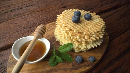 Waffles, blueberries, honey in a plate with a spoon, rosemary on a beautiful wooden table, mint leaves. Healthy food, beautiful still life Stok Fotoğraf