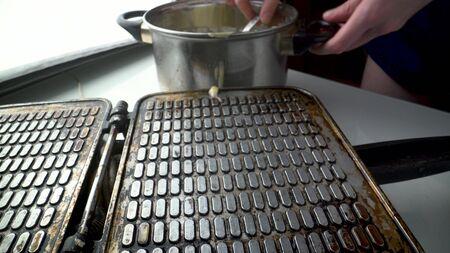 young woman making waffles at home.