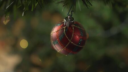 a glass toy hangs on a decorated Christmas tree, against the background of flashing lights.