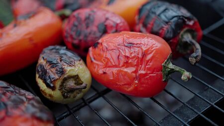 Peppers on outdoor grill closeup showing flames and smoke . Vegetables grill. Barbecue