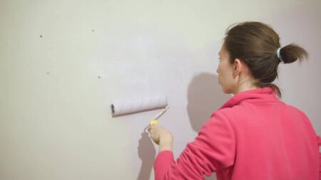 Happy beautiful young woman doing wall painting.