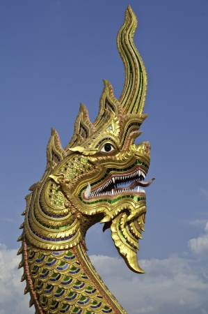 a golden statue of  naga fireball with blue sky photo