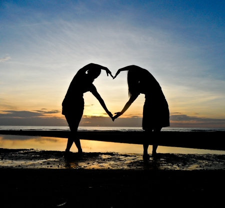 Two girls make heart with sea and sun down background