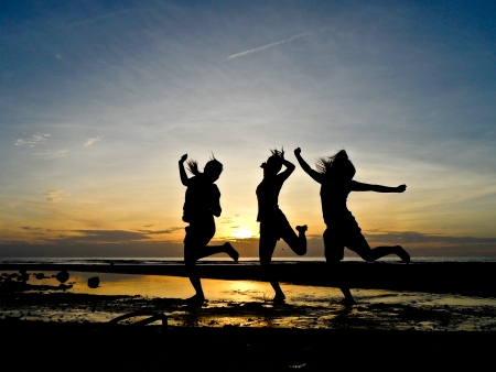 Three happy young poeple jump on the beach with twiling sky background Banco de Imagens