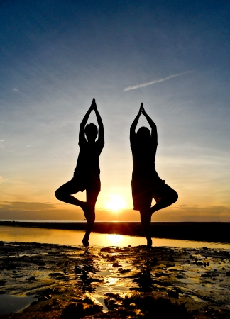 Two young women play yoga on the beach with twiling light photo