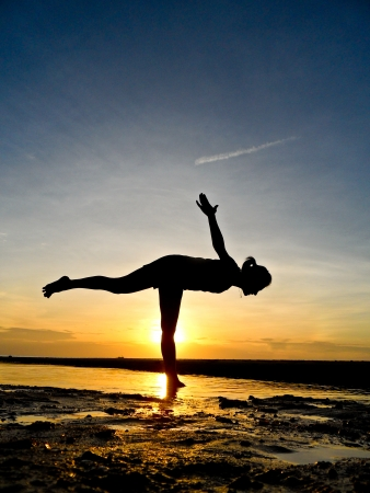 posture correction: Young woman play yoga on the beach with twiling light