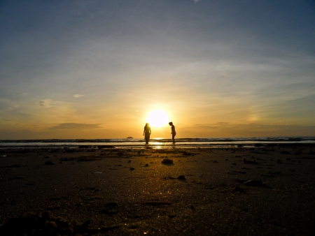 Two young people is walking on the beach with sunset background photo