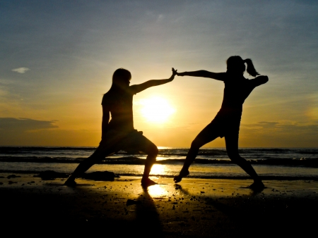Two young poeple play on the beach with sunset background photo