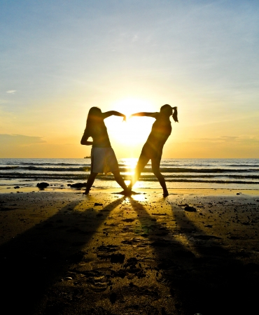 Two girls make heart with sea and sun down background photo