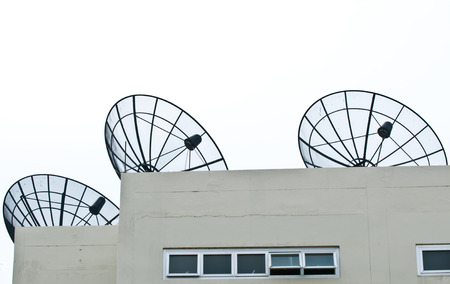 transmit: Three satellight dish on grey building with glass windows and white background