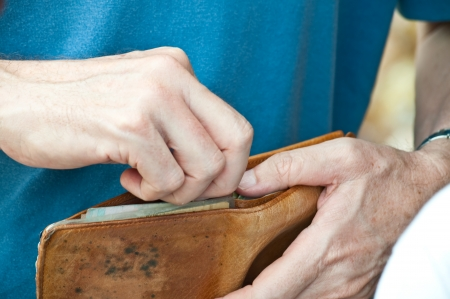 Two hands are opening brown purse to get money photo