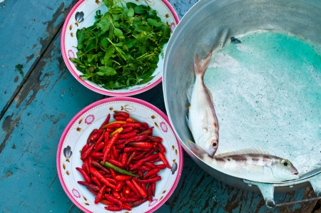 Two fresh fish in pot and red chili and basil on blue wood photo