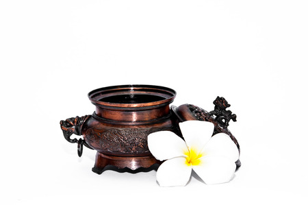 Ancient container with flower and lion on top photo