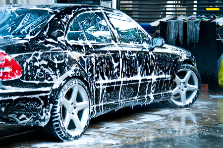 Beauty black car with soap in car wash photo