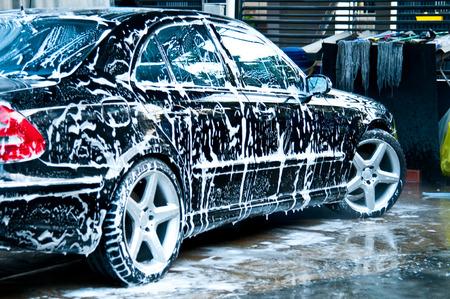 Schoonheid zwarte auto met zeep in wasstraat