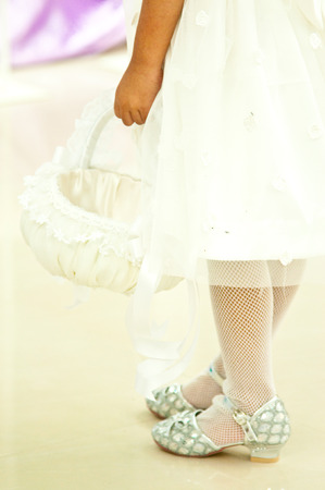 Flower girl carries white flower basket